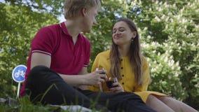 Pares felices jovenes en el amor que hace comida campestre con el vino en el jardín o el parque floreciente hermoso que charla y  metrajes