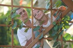 Pares felices jovenes en el cedazo de madera Foto de archivo