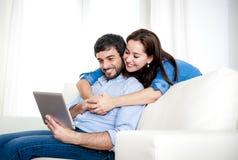 Pares felices jovenes en el sofá en casa que goza con la tableta digital Imágenes de archivo libres de regalías