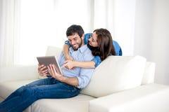 Pares felices jovenes en el sofá en casa que goza con la tableta digital Imagenes de archivo