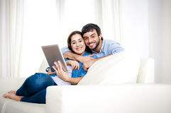 Pares felices jovenes en el sofá en casa que goza con la tableta digital Fotos de archivo