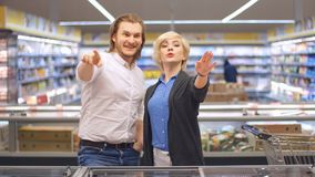 Pares felices jovenes en el supermercado que elige los productos para una celebración de familia almacen de video