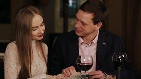 Pares felices jovenes en menú de la lectura del restaurante almacen de metraje de vídeo