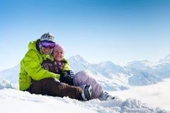 Pares felices jovenes en montañas del invierno Imagen de archivo libre de regalías