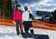 Pares felices jovenes en trajes de esquí, cascos y la colocación de las gafas del esquí Imagen de archivo