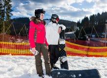 Pares felices jovenes en trajes de esquí, cascos y suplente de las gafas del esquí Imagen de archivo
