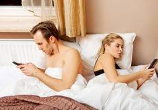 Pares felices jovenes en una cama con los teléfonos móviles Imagenes de archivo