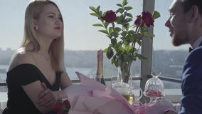 Pares felices jovenes hermosos sentarse en el restaurante del tejado en la tabla con las flores y hablar Fecha perfecta metrajes