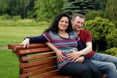 Pares felices jovenes (mujer embarazada) en banco Fotografía de archivo