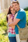 Pares felices jovenes que abrazan en parque asoleado Foto de archivo libre de regalías