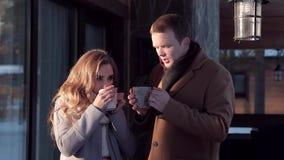 Pares felices jovenes que beben una bebida caliente en el pórtico en el invierno metrajes