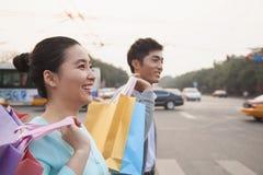 Pares felices jovenes que caminan abajo de la calle con los bolsos de compras coloridos en Pekín Foto de archivo libre de regalías