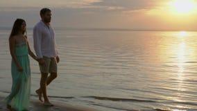 Pares felices jovenes que caminan cerca del mar en la puesta del sol Concepto de amor almacen de video