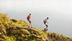 Pares felices jovenes que caminan con las mochilas en Rocky Trail hermoso en Sunny Evening Viaje y aventura de la familia fotografía de archivo libre de regalías