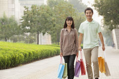 Pares felices jovenes que caminan con los bolsos de compras coloridos en manos en Pekín, China Foto de archivo libre de regalías
