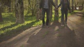 Pares felices jovenes que caminan en el parque de la ciudad, disfrutando de la fecha romántica afuera almacen de video
