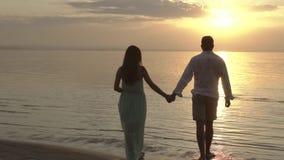 Pares felices jovenes que caminan en la playa en la puesta del sol Concepto de amor almacen de metraje de vídeo