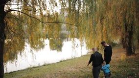 Pares felices jovenes que caminan en parque del otoño Una madre joven con un papá joven que detiene al niño pequeño de las manos  almacen de metraje de vídeo