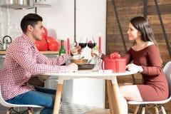 Pares felices jovenes que celebran día del ` s de la tarjeta del día de San Valentín con una cena en casa que tuesta con el vino Imagen de archivo libre de regalías