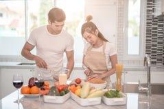 Pares felices jovenes que cocinan junto en la cocina en casa imagen de archivo