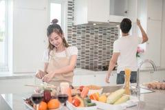 Pares felices jovenes que cocinan junto en la cocina en casa foto de archivo