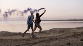 Pares felices jovenes que corren con la granada de humo coloreado en sus manos por el mar durante puesta del sol Diversión, humo  almacen de video