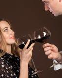 Pares felices jovenes que gozan de vidrios de vino rojo Imagen de archivo