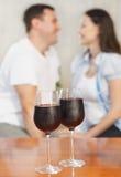 Pares felices jovenes que gozan de vidrios de vino rojo Imagenes de archivo