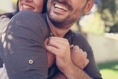Pares felices jovenes que gozan junto en parque de la ciudad Fotos de archivo
