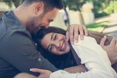 Pares felices jovenes que gozan junto en parque de la ciudad Imagen de archivo