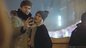 Pares felices jovenes que hacen el selfie del invierno al aire libre almacen de video