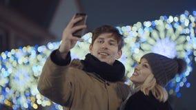 Pares felices jovenes que hacen el selfie del invierno al aire libre almacen de metraje de vídeo