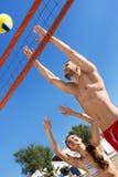 Pares felices jovenes que juegan a voleibol Imagen de archivo libre de regalías