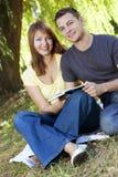 Pares felices jovenes que leen un libro Fotografía de archivo libre de regalías