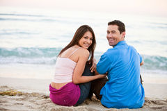 Pares felices jovenes que llevan a cabo las manos en la playa Imagen de archivo