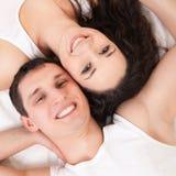 Pares jovenes que mienten en la cama blanca Imagen de archivo libre de regalías