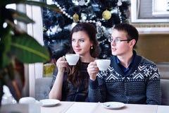 Pares felices jovenes que miran en un lado que sostiene una taza Árbol de navidad Foto de archivo libre de regalías