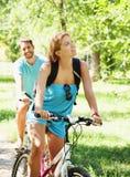 Pares felices jovenes que montan una bicicleta imagen de archivo