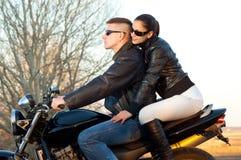 Pares felices jovenes que montan una motocicleta Imagen de archivo libre de regalías