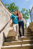 Pares felices jovenes que recorren abajo de la sonrisa de las escaleras Fotografía de archivo