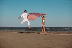 Pares felices, jovenes que recorren a lo largo de la costa Fotos de archivo libres de regalías