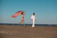 Pares felices, jovenes que recorren a lo largo de la costa Fotos de archivo