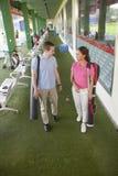 Pares felices jovenes que salen del campo de golf con los clubs de golf y el carrito Fotos de archivo