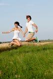 Pares felices jovenes que saltan afuera en verano foto de archivo