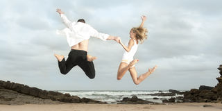 Pares felices jovenes que saltan para la alegría en la playa foto de archivo