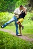 Pares felices jovenes que se besan en un parque Fotos de archivo