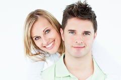 Pares felices jovenes que se colocan sobre el fondo blanco Imágenes de archivo libres de regalías