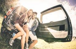 Pares felices jovenes que se divierten con el teléfono móvil en el viaje por carretera del coche Foto de archivo libre de regalías