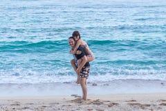 Pares felices jovenes que se divierten en una playa blanca tropical del ` s del centro turístico de la isla de Bali, Indonesia Foto de archivo libre de regalías