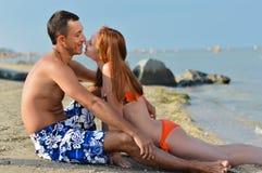 Pares felices jovenes que se relajan y que se besan en el abarcamiento arenoso de la playa del mar Imágenes de archivo libres de regalías